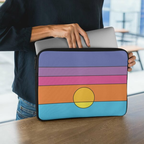 person holding a laptop sleeve with a colorful minimalist sunset design