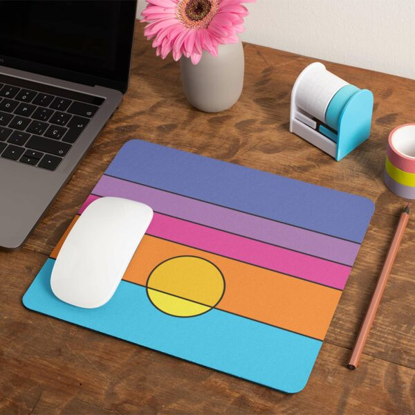 mouse pad with a colorful minimalist sunset design on a desk next to a laptop