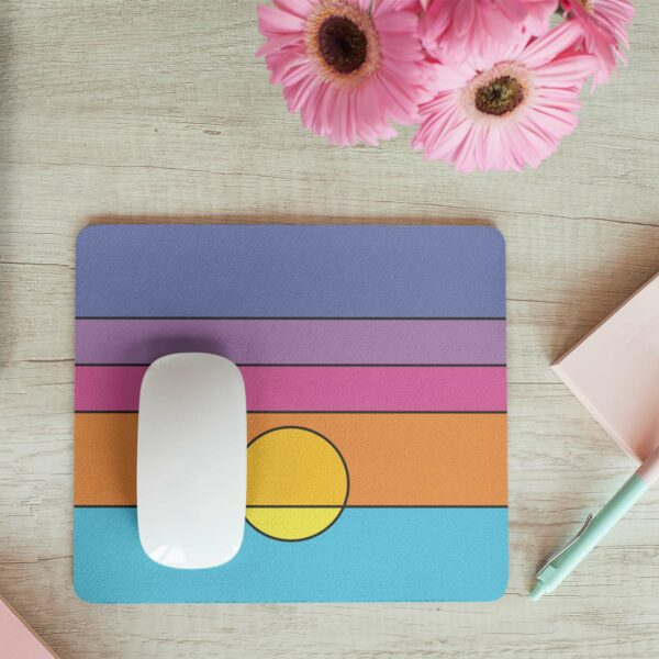 mouse pad with a colorful minimalist sunset design on a desk next to flowers