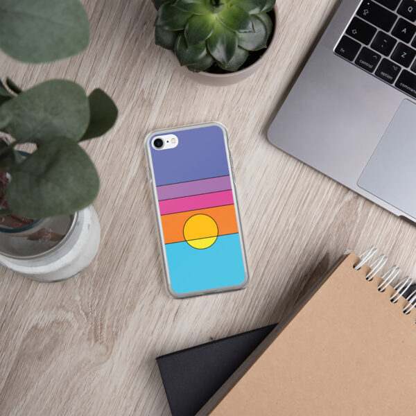 iphone case with a colorful minimalist sunset design sitting on a desk with a laptop