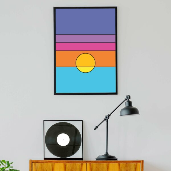 vertical art print with a colorful minimalist sunset design in a black frame hanging on a wall above a turntable