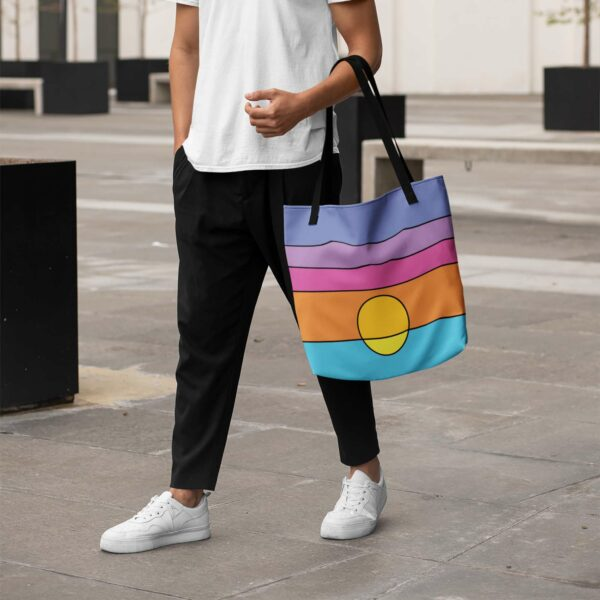 person walking outside and holding a tote bag with a colorful minimalist sunset design and black handles