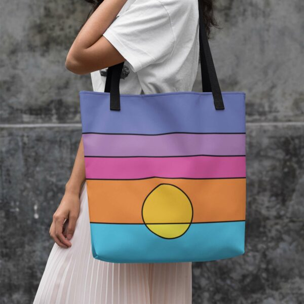 woman holding a tote bag with a colorful minimalist sunset design and black handles