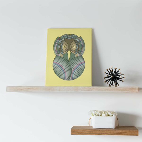 vertical stretched canvas art print with a colorful green and brown owl design on a yellow background sitting on a shelf