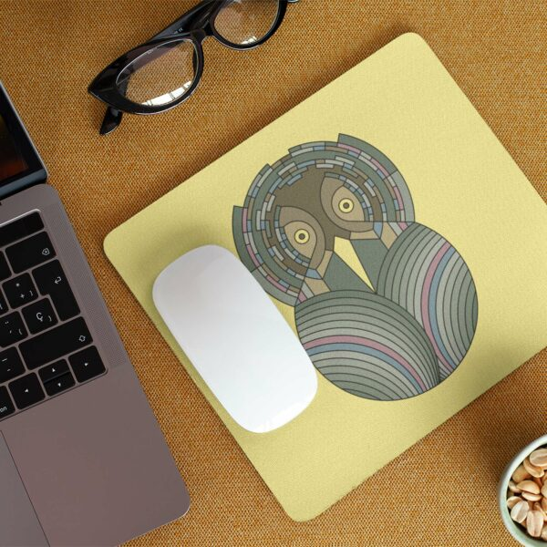 mouse pad with a colorful green and brown owl design on a yellow background on a desk next to a laptop
