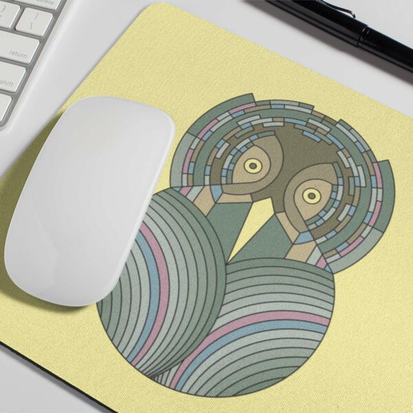 mouse pad with a colorful green and brown owl design on a yellow background with a white mouse on top