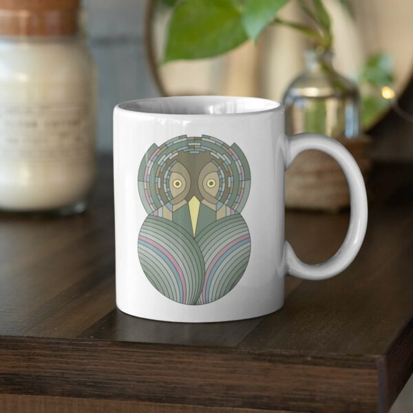 white ceramic coffee mug with a colorful green and brown owl design sitting on a table
