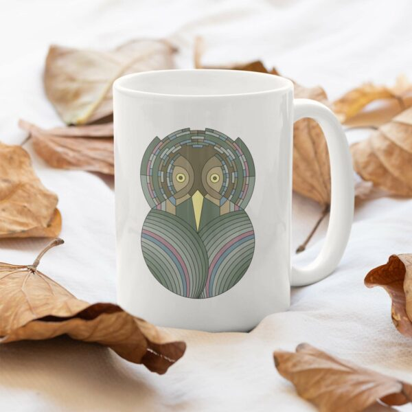 white ceramic coffee mug with a colorful green and brown owl design sitting in a pile of leaves
