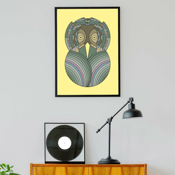 vertical art print with a colorful green and brown owl design on a yellow background in a black frame hanging on a wall above a turntable