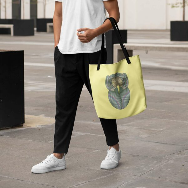 person walking and holding a yellow tote bag with black handles and a green and brown owl design on the side