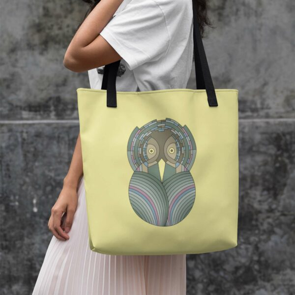 woman holding a yellow tote bag with black handles and a green and brown owl design on the side