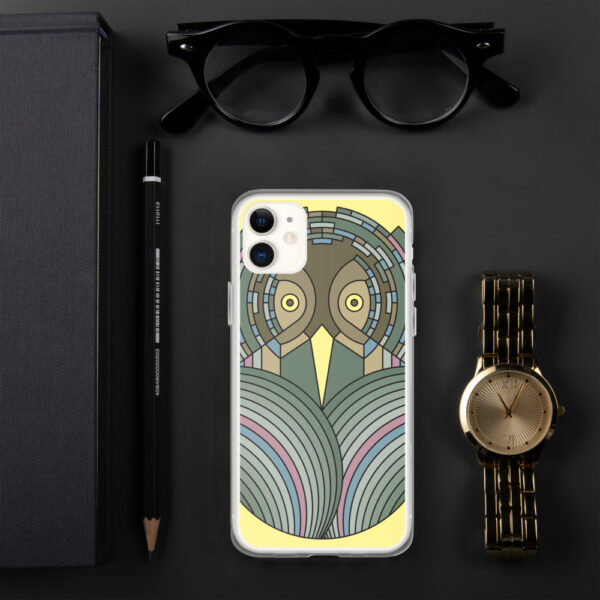iphone case with a colorful green and brown owl design sitting on a desk next to a watch
