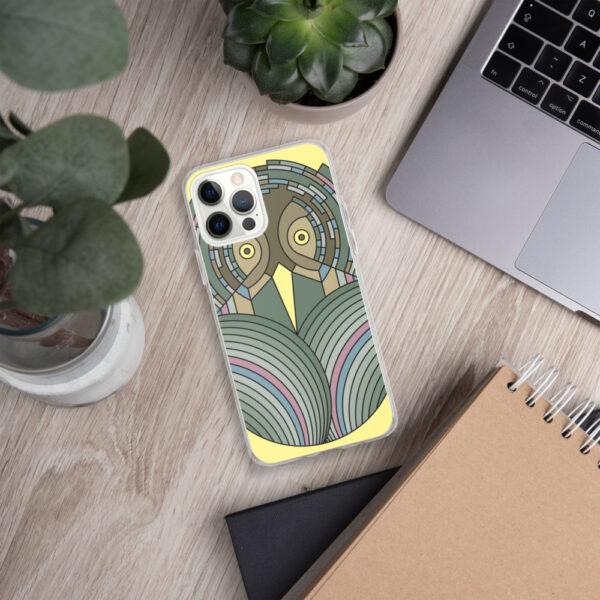 iphone case with a colorful green and brown owl design sitting on a desk next to a laptop