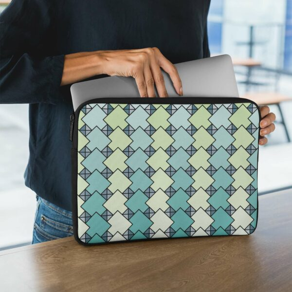 person holding a laptop sleeve with a blue and green tile pattern