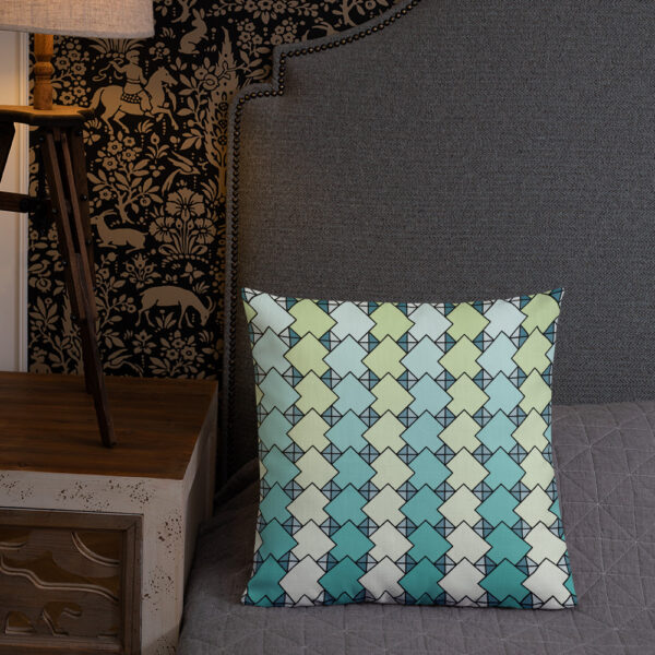 square pillow with a blue and green tile pattern on a bed
