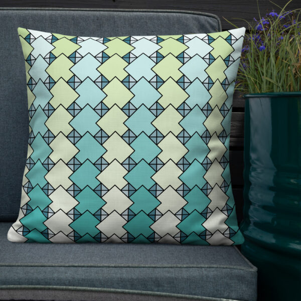 square pillow with a blue and green tile pattern on a seat next to a plant