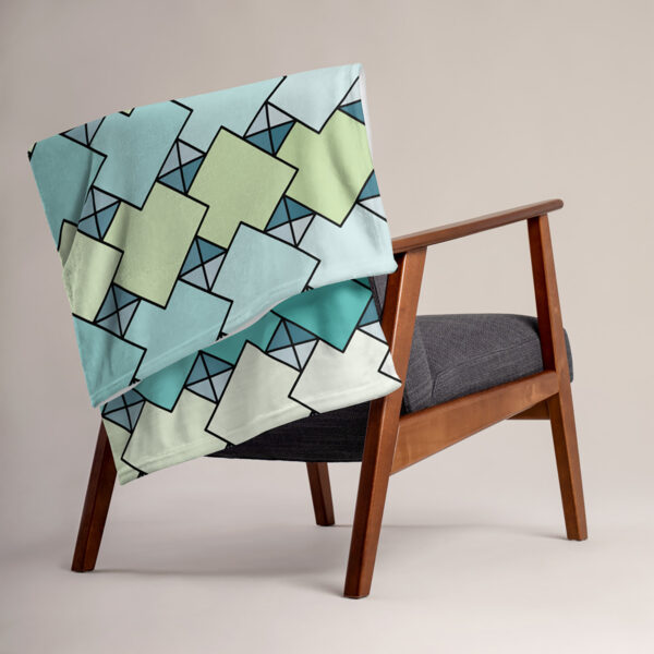 blanket with a blue and green tile pattern draped over a chair
