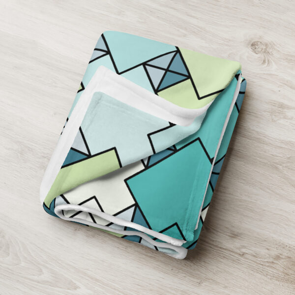 folded blanket with a blue and green tile pattern