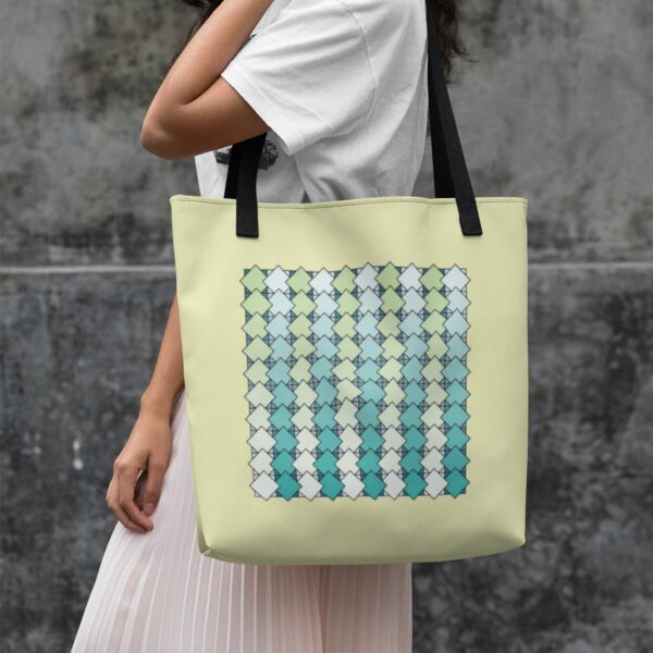 woman holding a tote bag with a blue and green tile pattern on a yellow background and black handles