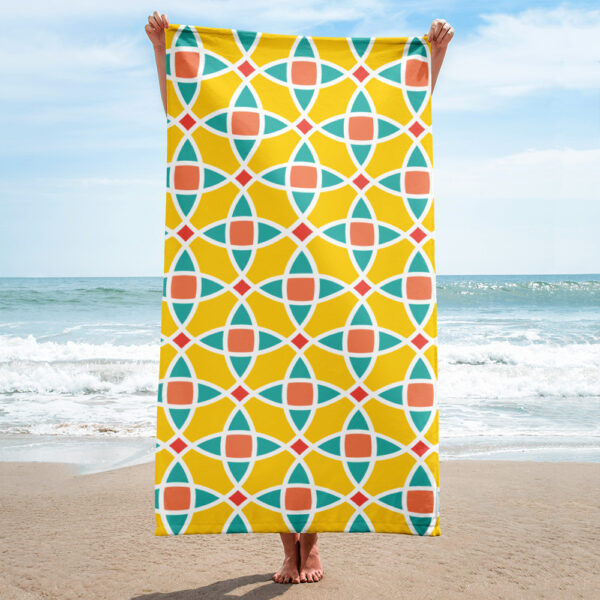 person on a beach holding a beach towel with a yellow blue and orange mosaic tile pattern