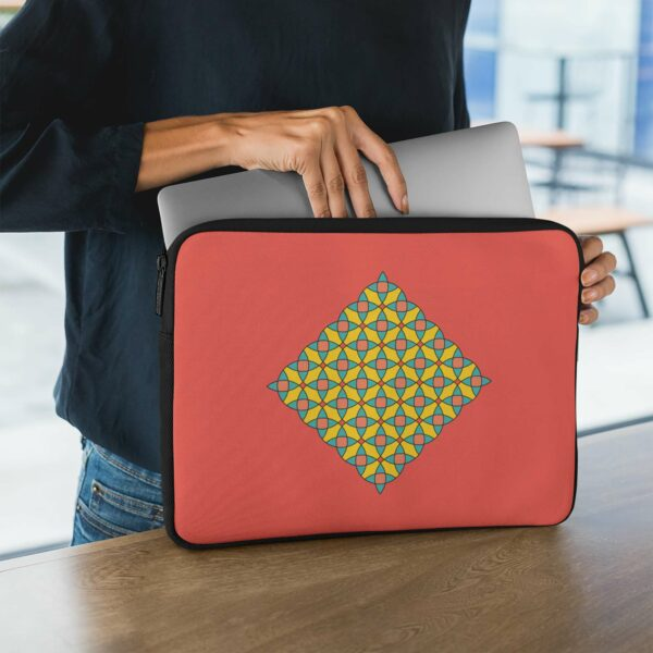 person holding a laptop sleeve with a yellow mosaic design on a red background