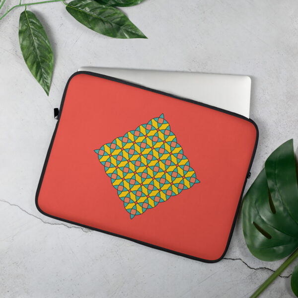 laptop sleeve with a yellow mosaic design on a red background sitting on a table