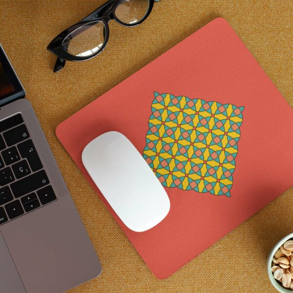 mouse pad with a yellow blue and orange mosaic design on a red background on a desk with a computer mouse