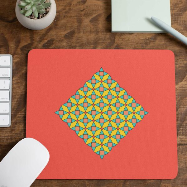 mouse pad with a yellow blue and orange mosaic design on a red background on a desk with a note pad
