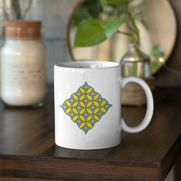 white ceramic coffee mug with a colorful mosaic design on the side sitting on a table