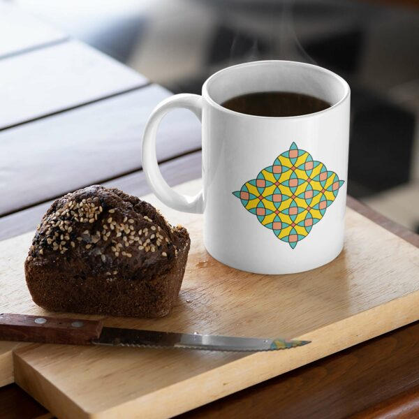 white ceramic coffee mug with a colorful mosaic design on the side sitting on a cutting board