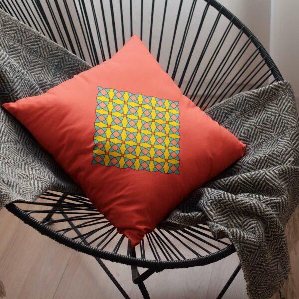red square pillow with a yellow orange and blue mosaic design sitting on a chair