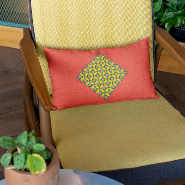 red rectangle pillow with a yellow orange and blue mosaic design sitting on a chair