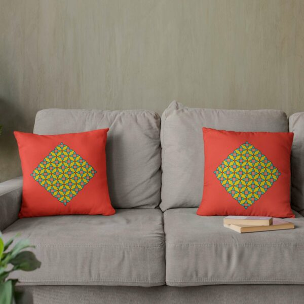two red square pillows with a yellow orange and blue mosaic design sitting on a sofa