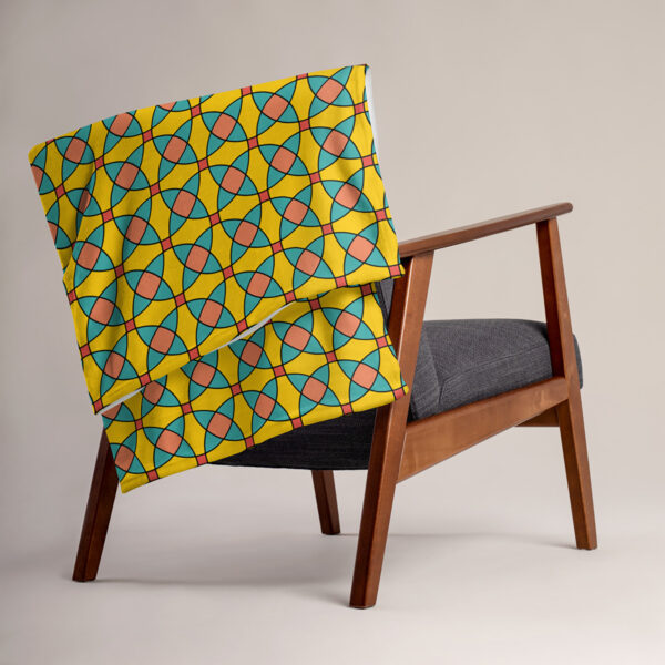 blanket with a yellow orange and blue mosaic tile pattern draped over a chair
