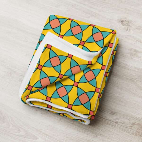 folded blanket with a yellow orange and blue mosaic tile pattern