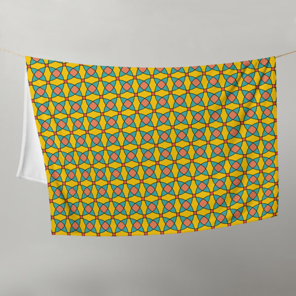 blanket with a yellow orange and blue mosaic tile pattern hanging on a clothes line