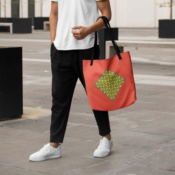 person holding a red tote bag with a yellow orange and blue mosaic design in the center and black handles