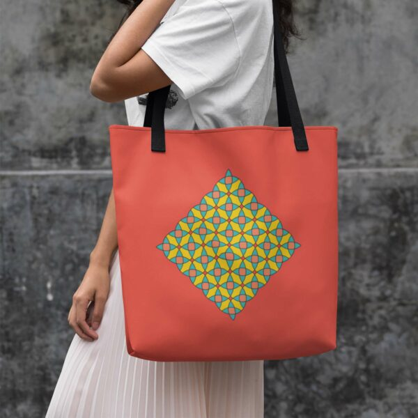 woman holding a red tote bag with a yellow orange and blue mosaic design in the center and black handles