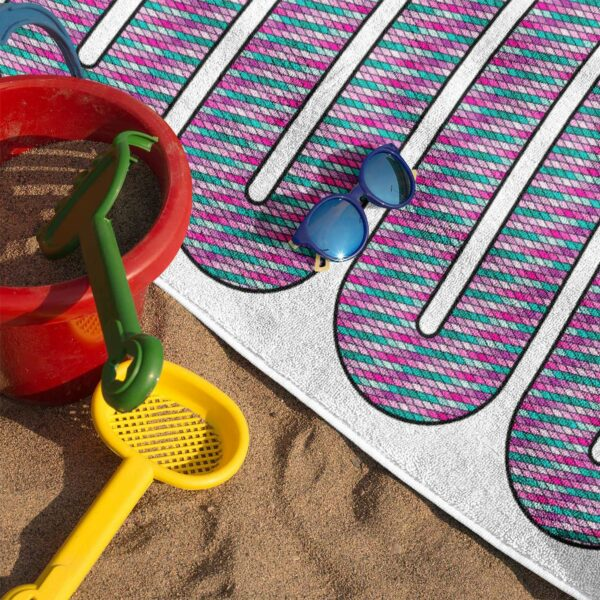 beach towel with a colorful pink snake design on sand with sunglasses