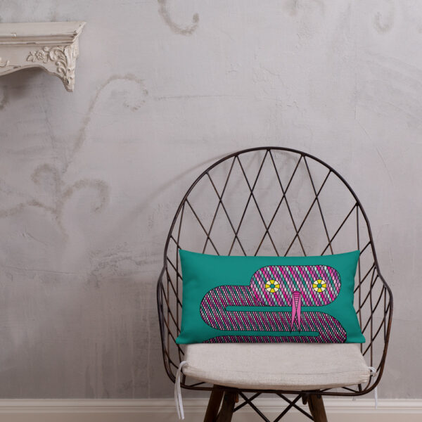 rectangle pillow with a pink snake design on a teal blue background sitting on a chair