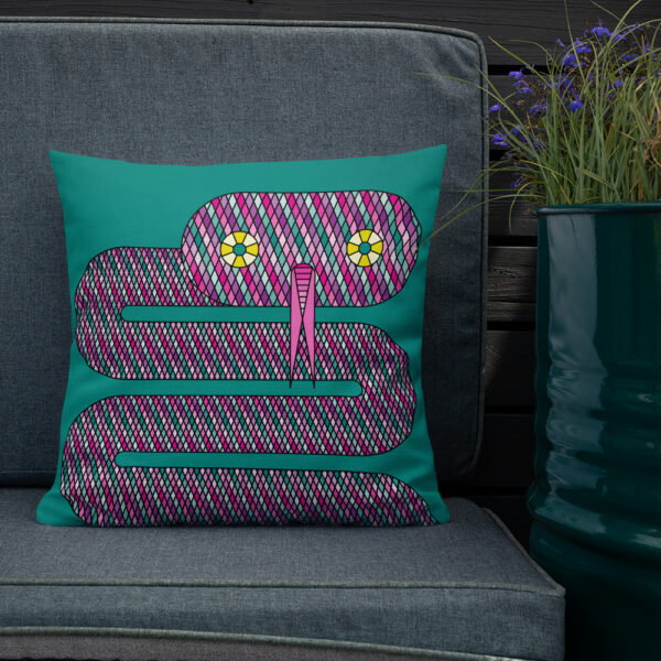 square pillow with a pink snake design on a teal blue background sitting on a chair next to a plant