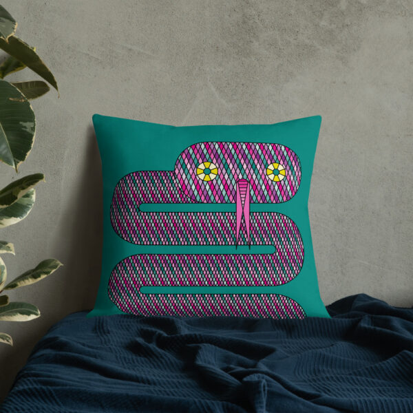 square pillow with a pink snake design on a teal blue background sitting on a bed