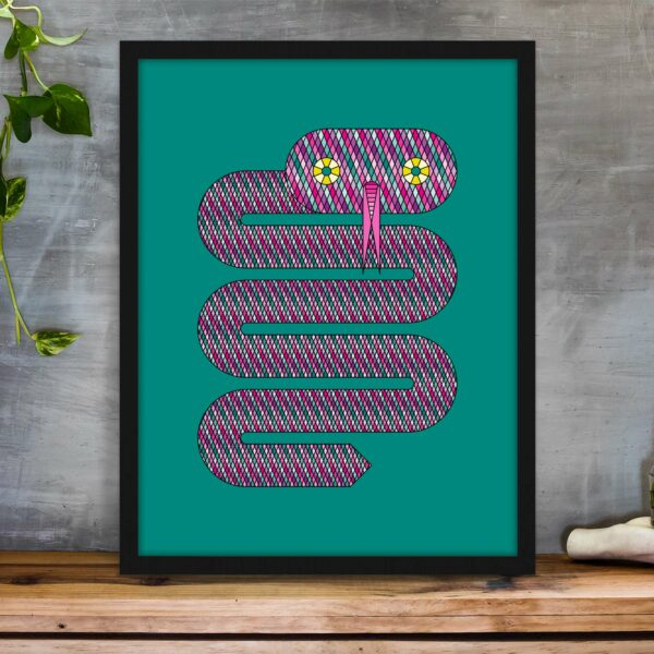 vertical fine art print of a pink snake on a teal blue background in a black frame on a table