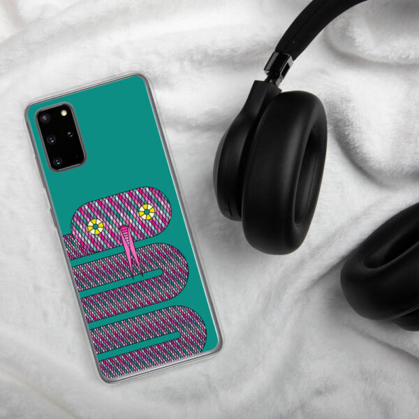 samsung phone case with a design of a pink snake on a teal blue background sitting next to headphones