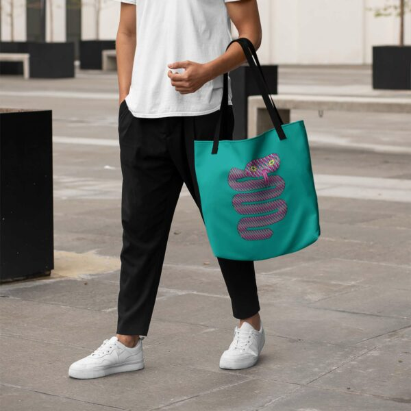 person holding a teal blue tote bag with a pink snake design and black handles