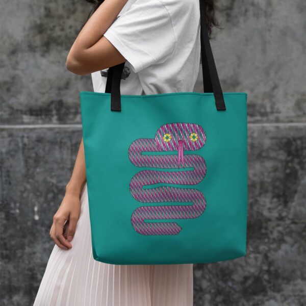 woman holding a teal blue tote bag with a pink snake design and black handles