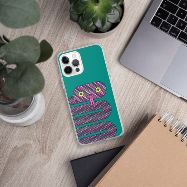 iphone case with a design of a pink snake on a teal blue background sitting next to a laptop