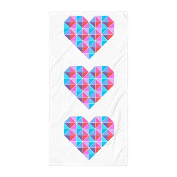 beach towel with a colorful design of three pink and blue hearts