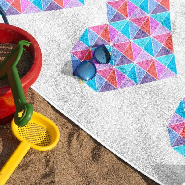 beach towel with a colorful design of three pink and blue hearts on sand with sunglasses