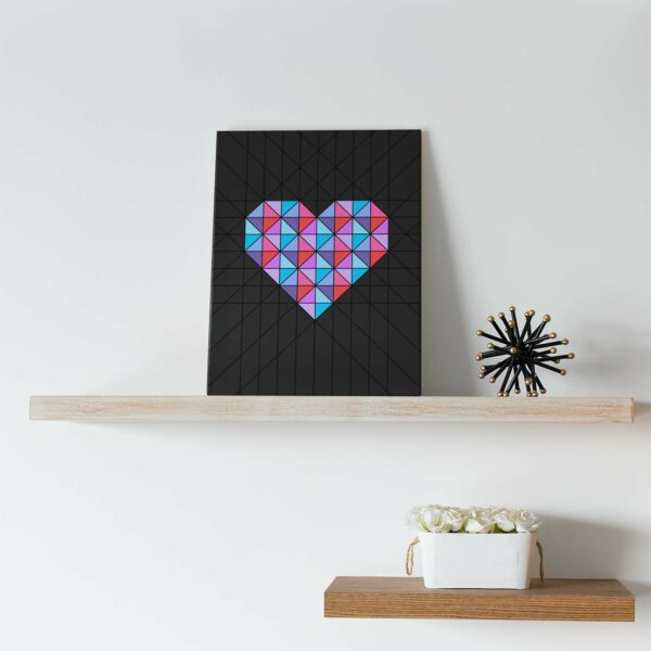 vertical stretched canvas art print of a pink and blue geometric heart design on a black background on a shelf